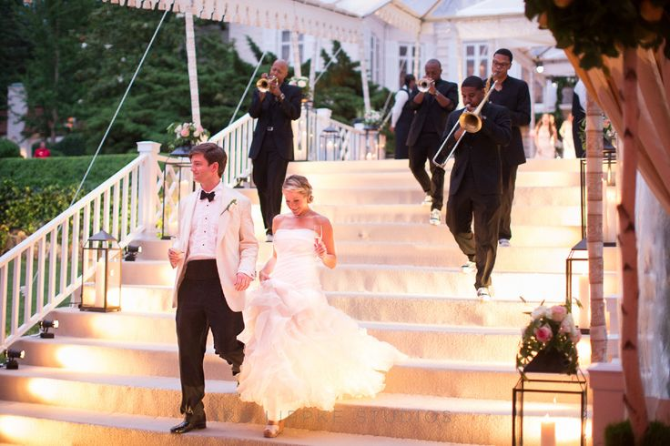 bride and groom walking down stairs with band playing walking behind them