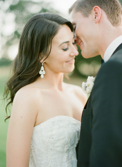 bride and groom about to kiss, bride wearing chandelier earrings in strapless wedding dress