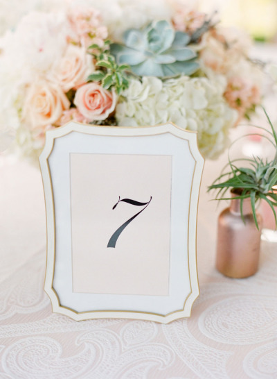 wedding table number with blush and green wedding bouquet in the backdrop