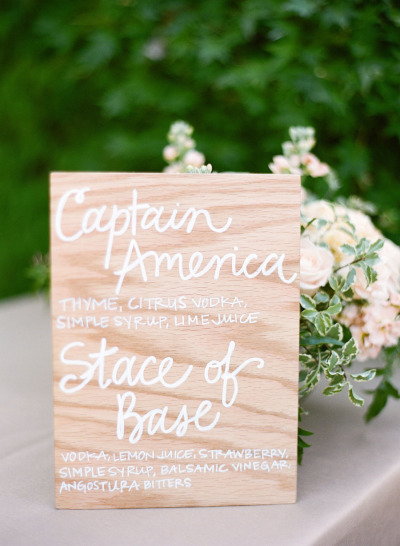 wood signature cocktail sign with white writing and blush and green florals