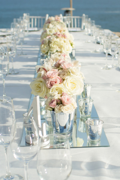 white kings table by the ocean with white and pink low flowers