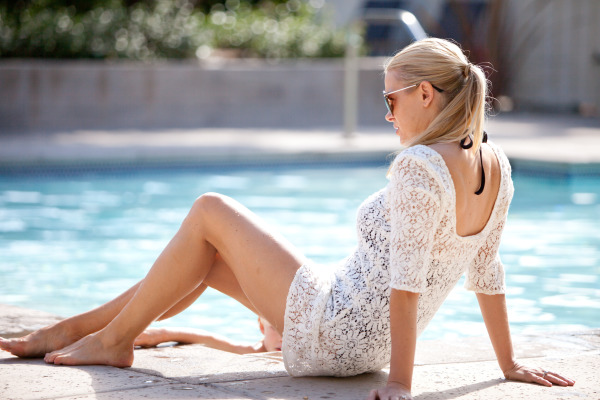 girl laying by the pool in white lace coverup