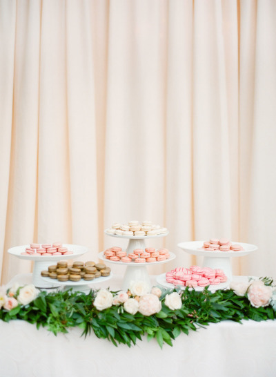 wedding table filled with macaroon serving trays, sweets table decorated with greenery