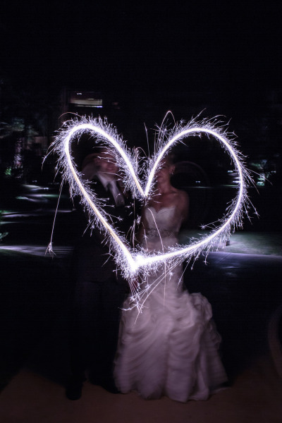 bride and groom make a heart out of sparklers