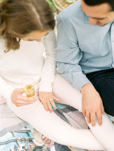 couple sitting on blanket looking at engagement ring