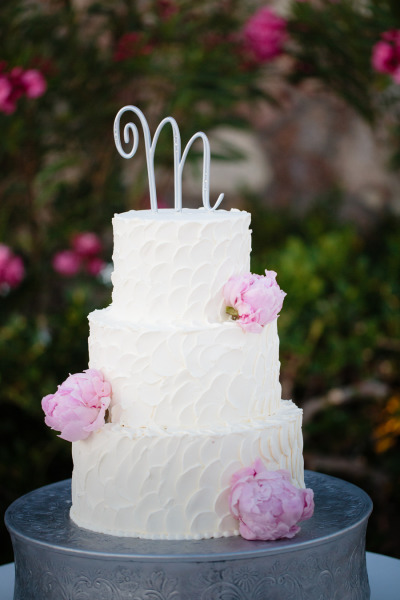 white wedding cake with pink peonies and a silver letter on top