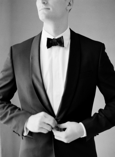groom buttoning up formal tux