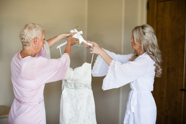 mother of the bride and bride holding up wedding dress