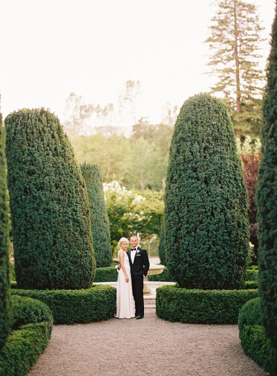 bride and groom standing next to tall hedges