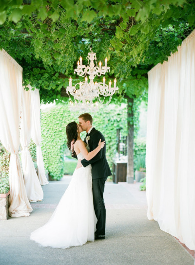 bride and groom kissing under greenery ceiling with chandeliers