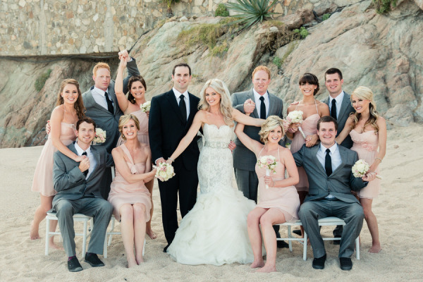 bride and groom posing with bridal party on the beach, groomsmen in grey suits, bridesmaids in short peach dresses and bride in mermaid lazaro lace dress