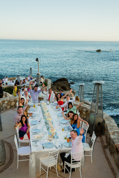 guests cheering at reception table on the ocean as bride and groom make their entrance