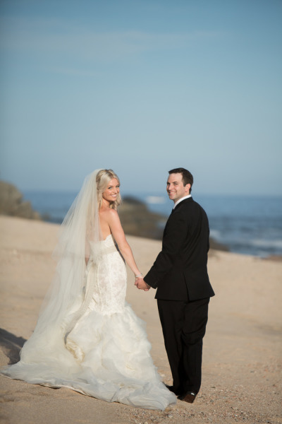 bride and groom on the beach looking back, bride in mermaid dress with bridal belt and bow