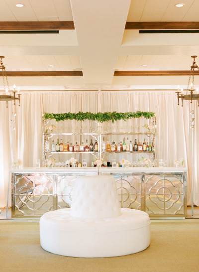 white wedding reception bar and greenery styling