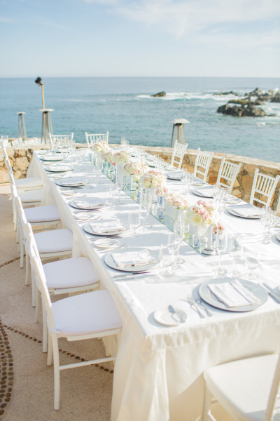 white tablescape with white chairs and low floral centerpieces by the ocean
