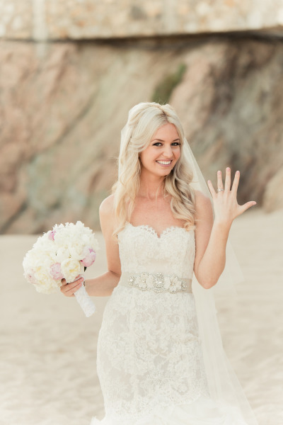 bride showing off wedding rind on the beach