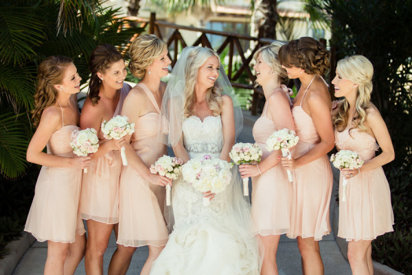 bride with bridesmaids laughing, bride in lace Lazaro wedding dress, and bridesmaids in short champagne dresses