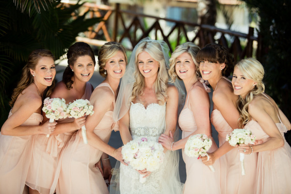 bride smiling with bridesmaids in peach Amsale dresses and bride in mermaid Lazaro 3201 dress