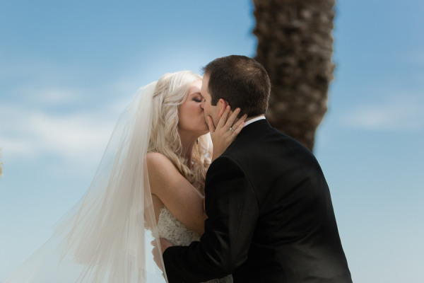 bride and groom kiss, bride holding grooms face