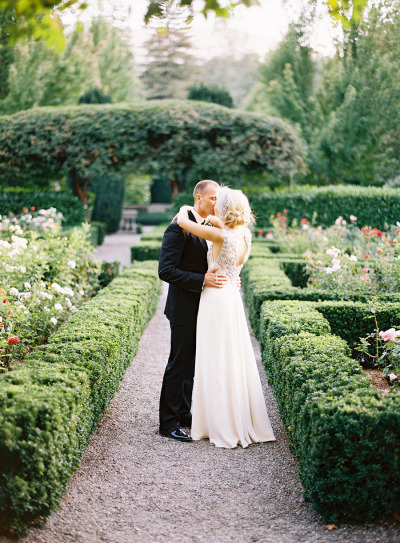 bride and groom kissing next to hedges