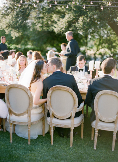bride and groom kissing during outdoor wedding reception