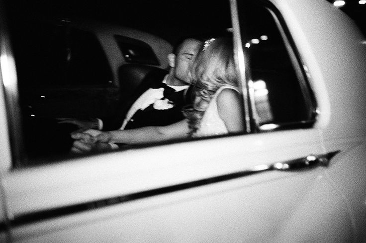 bride and groom kissing in white rolls royce