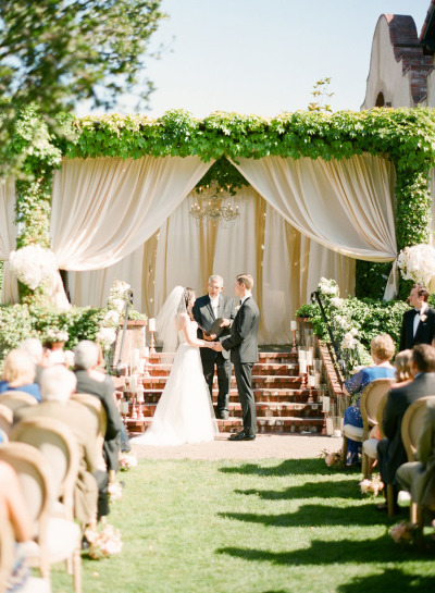 ceremony decor ideas, wedding ceremony with greenery arbor and white curtains and chandelier