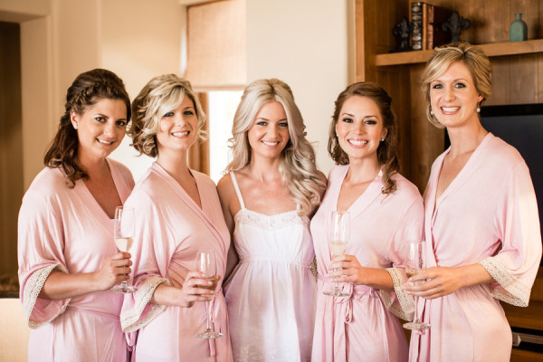 bride in white and bridesmaids in peach robes