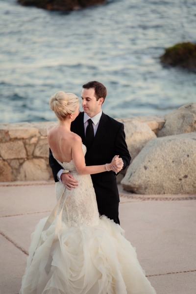 bride and groom dance by the ocean