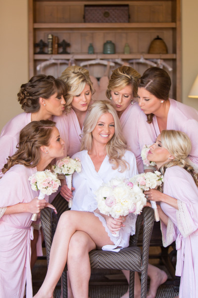 bridesmaids in pink robes all around bride in white robe