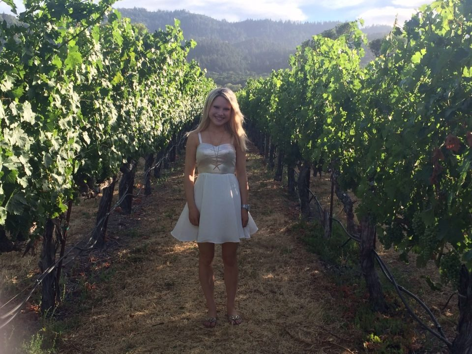 girl standing in a white dress in a vineyard