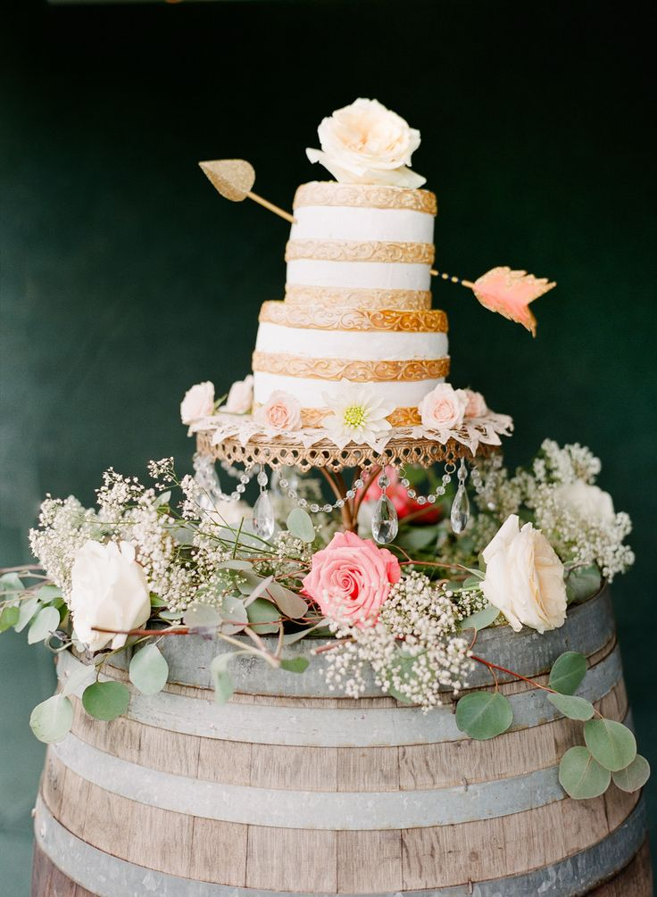 gold and white stripped cake with gold arrow through it on wine barrel