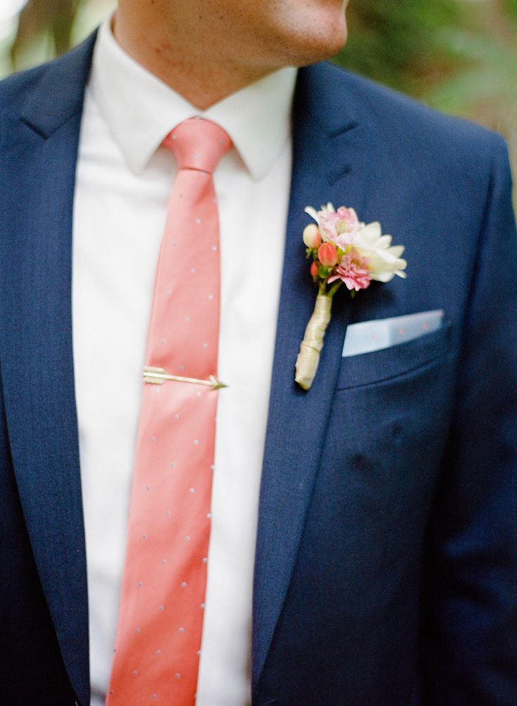 navy suit with coral tie and gold arrow tie stay