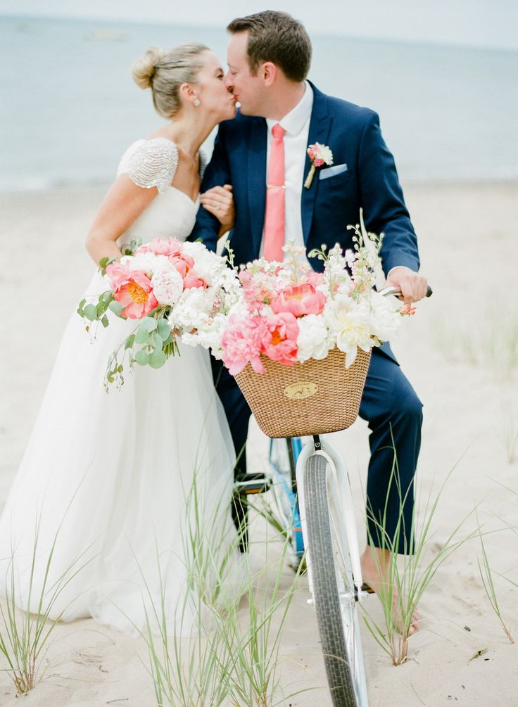 bride and groom kissing over beach cruiser bike with basket full of flowers