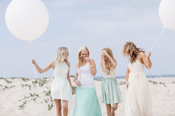 girls on sand dunes next to the ocean in cute dresses holding large white balloons