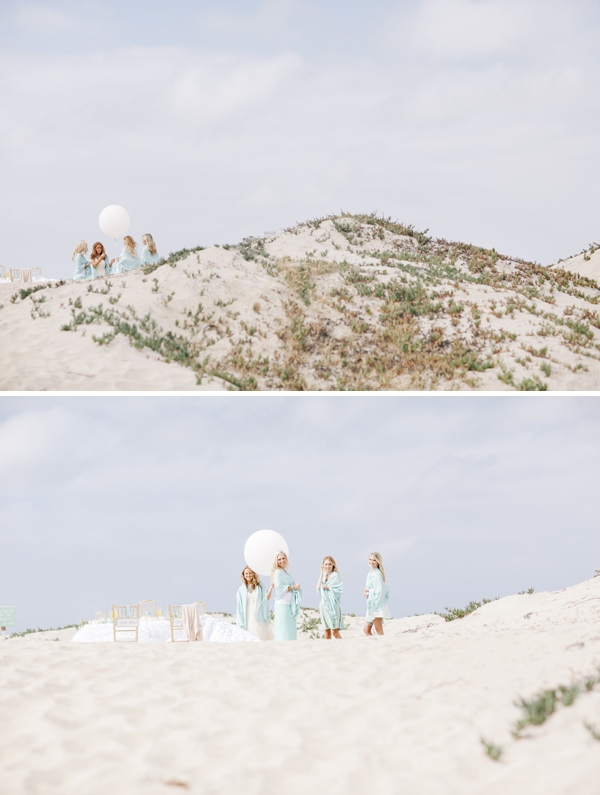 girls on sand dunes holding large white balloons