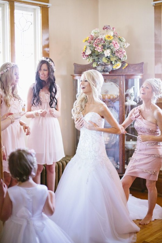 bride putting dress on around bridesmaids