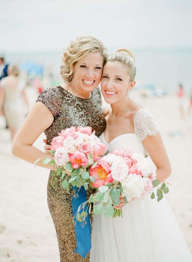 bride in reem acra dress with bridesmaid in long glittery dress holding pink bouquets of white and pink peonies on the beach