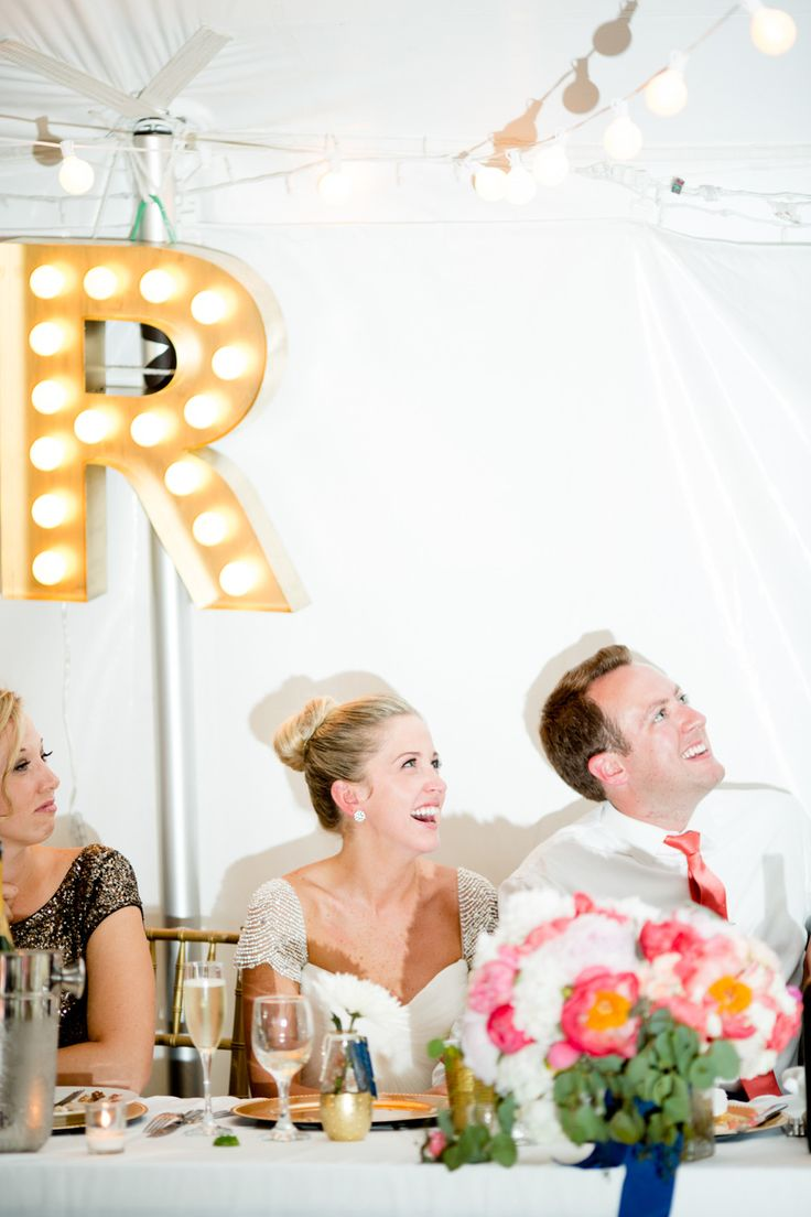 bride and groom at kings table with marquee letter decor