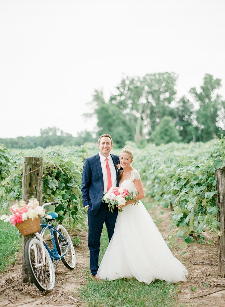 bride and groom standing in a vineyard , bride wearing top knot, beach cruiser with pink and white flowers