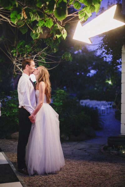 bride and groom kissing with light up arrow pointing at them