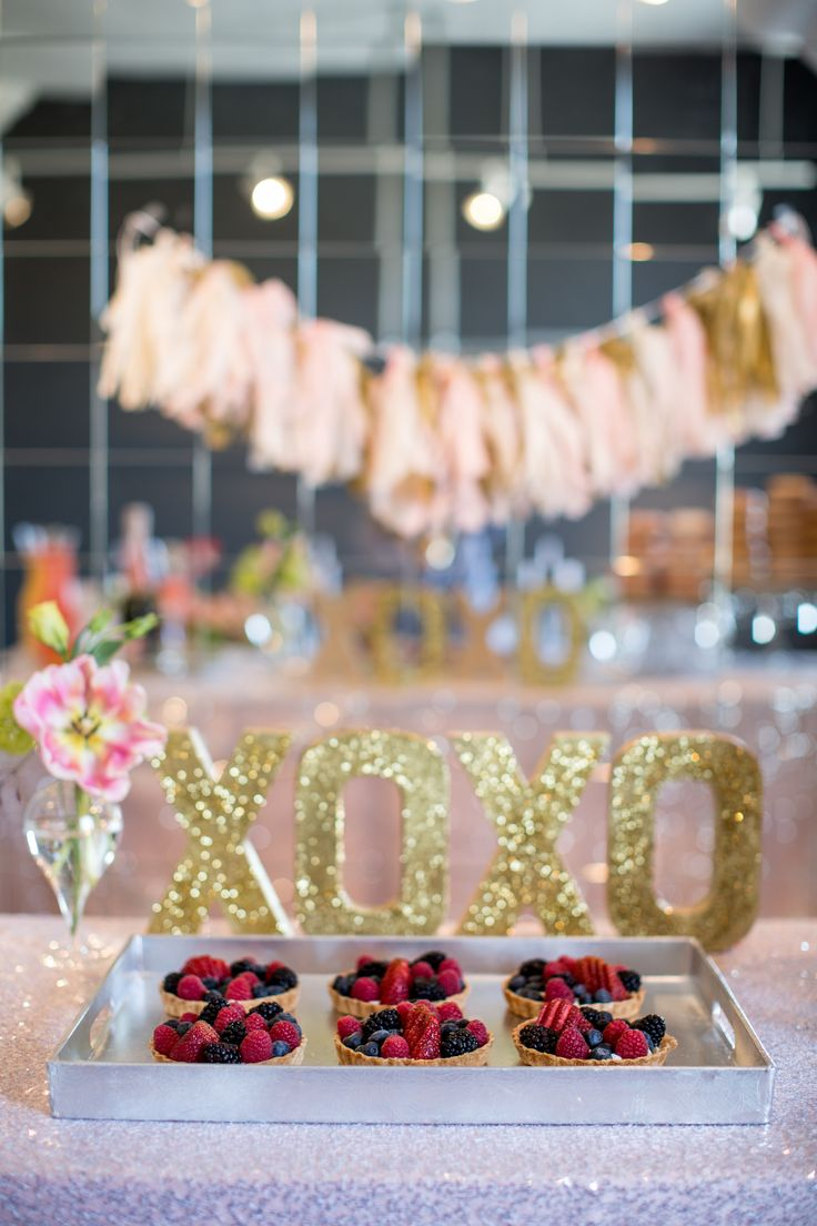 gold letters XOXO behind small fruit tarts
