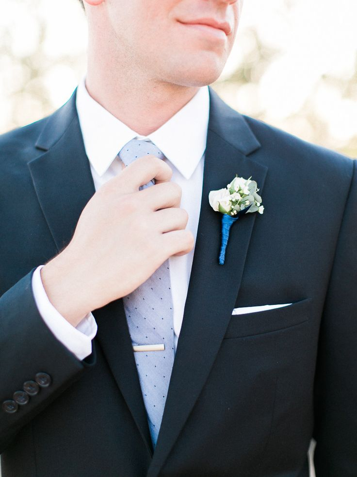 groom in black suit and light blue tie and royal blue boutonniere