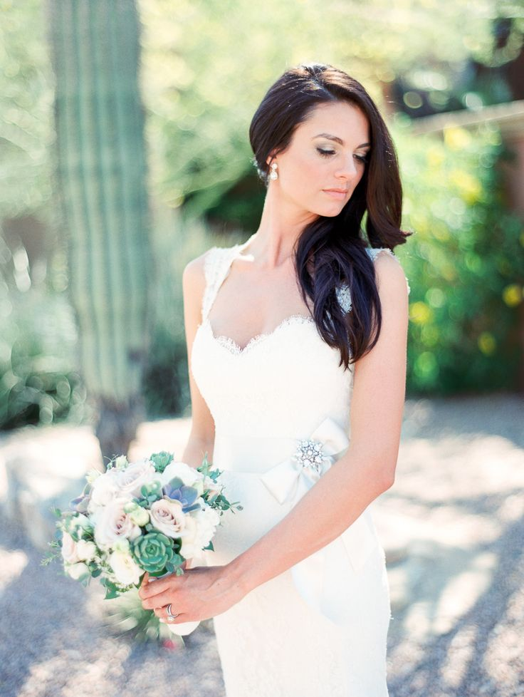 bride in lace wedding dress with satin bridal sash, bridal earrings