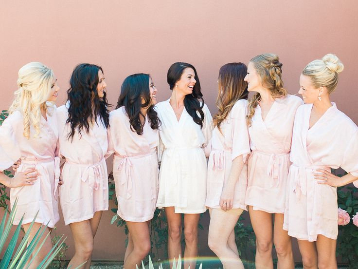 bride in white robe in the middle of bridesmaids in pink robes
