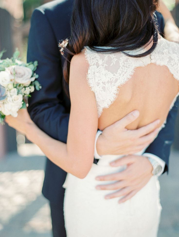 groom holding bride wearing lace keyhole wedding dress