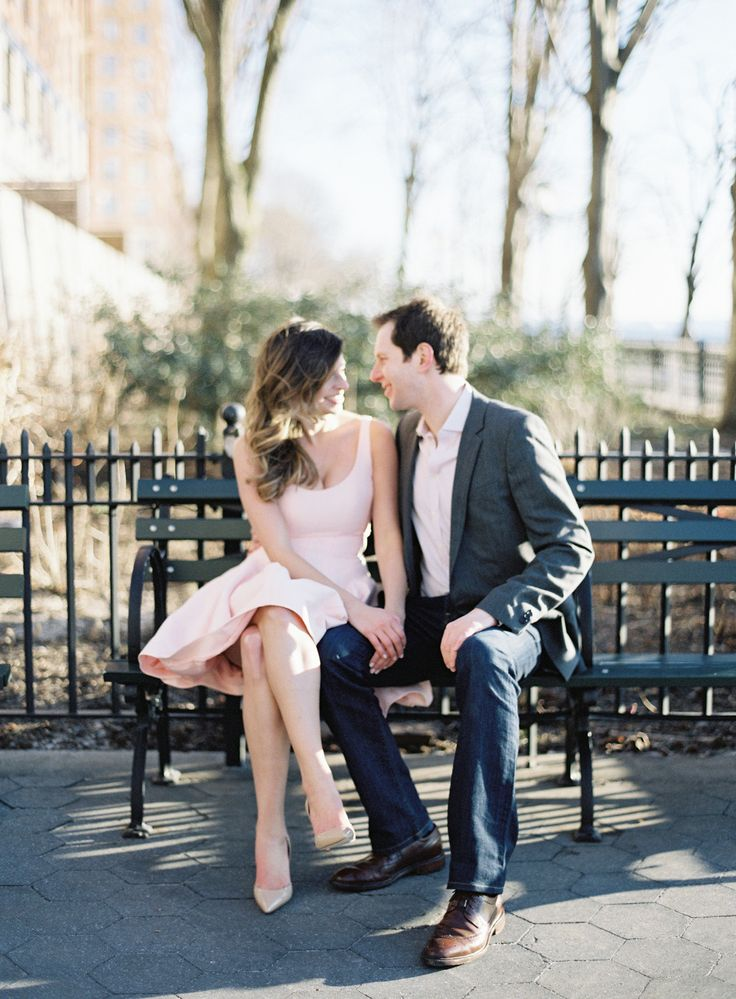 couple sitting on NYC park bench, girl in pink Halston Heritage dress, engagement photo ideas