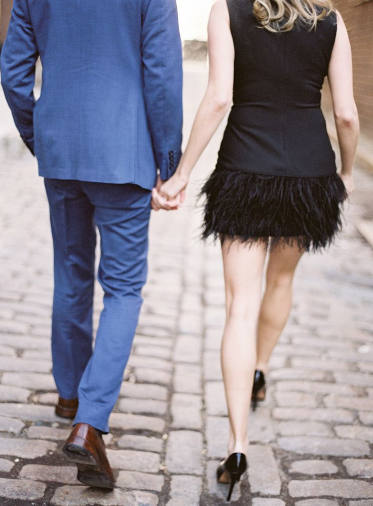 stylish couple walking on cobblestone in NYC, girl in black fringe dress