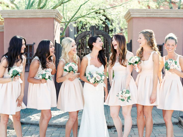 bride laughing with bridesmaids in short pink dresses holding bouquets