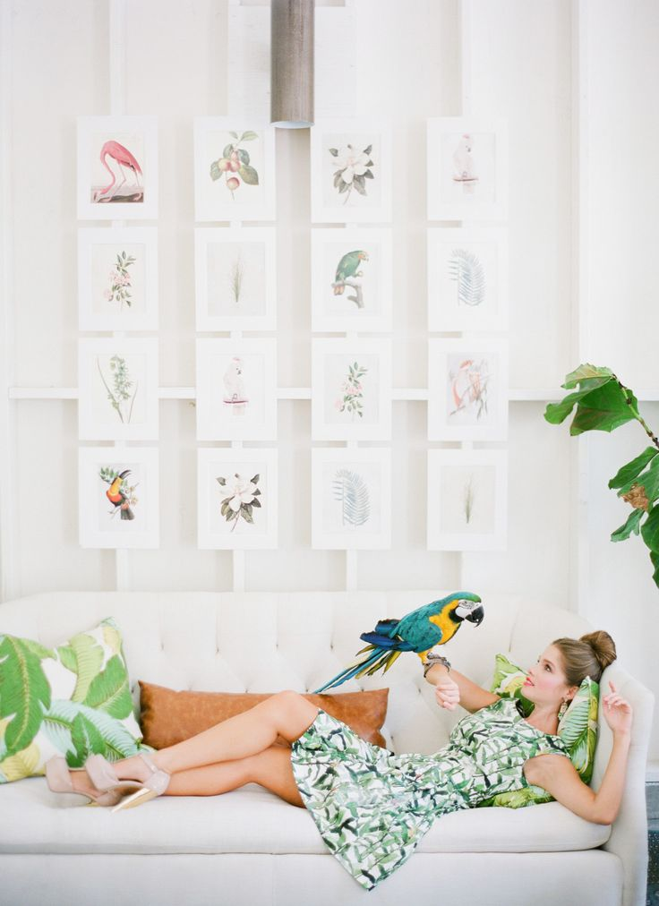 girl laying on a couch holding a parrot